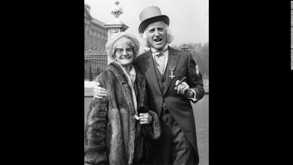 Savile and his mother pose outside Buckingham Palace in London, where he receive his Order of the British Empire in 1972.