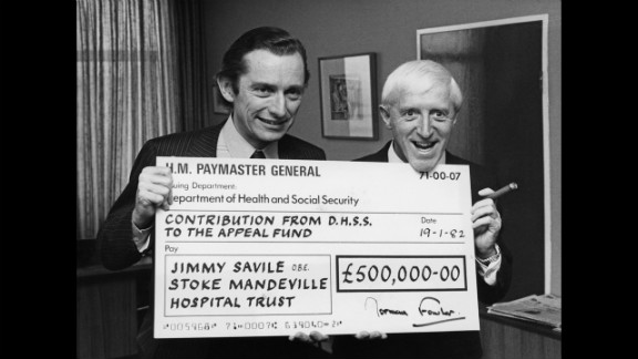 British Secretary of State for Social Services Norman Fowler presents Savile with a check for half a million pounds in 1982 as the government's contribution to an appeal for a new spinal injuries unit at Stoke Mandeville Hospital.