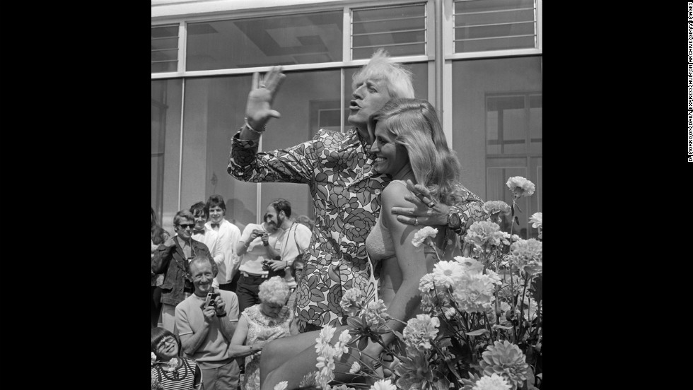 Savile waves with Jersey Holiday Queen Gaynor Lacey at the Jersey Battle of Flowers carnival in 1972.