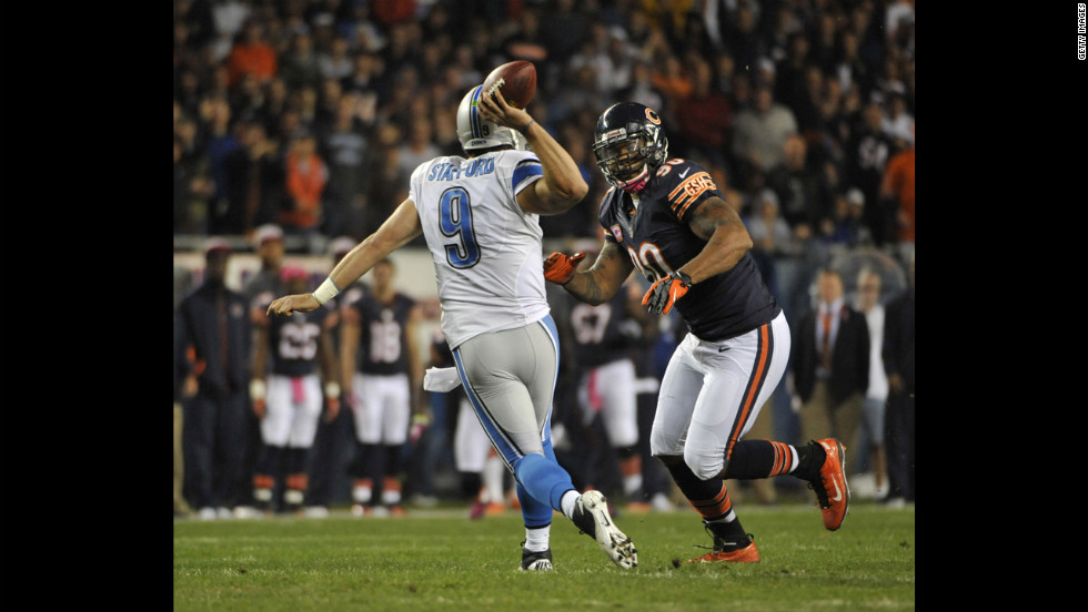 No. 90 Julius Peppers of the Bears pressures No. 9 Matthew Stafford of the Lions.