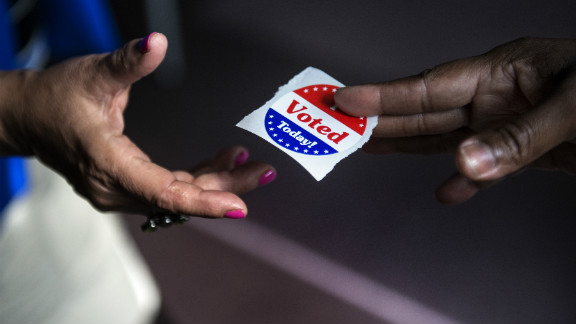 A poll worker hands out