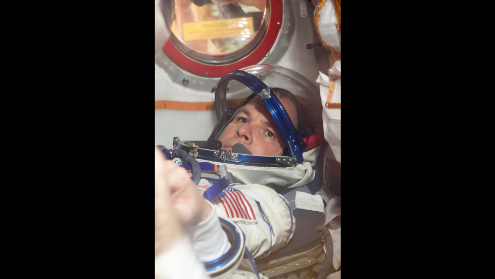 "Ford straps into a seat of the Soyuz spacecraft on October 10 during the first of two ""fit check"" dress rehearsal sessions."