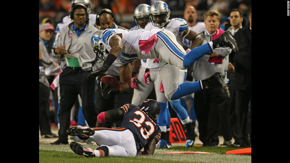 No. 87 Brandon Pettigrew of the Lions is hit and flipped out of bounds by No. 33 Charles Tillman of the Bears.