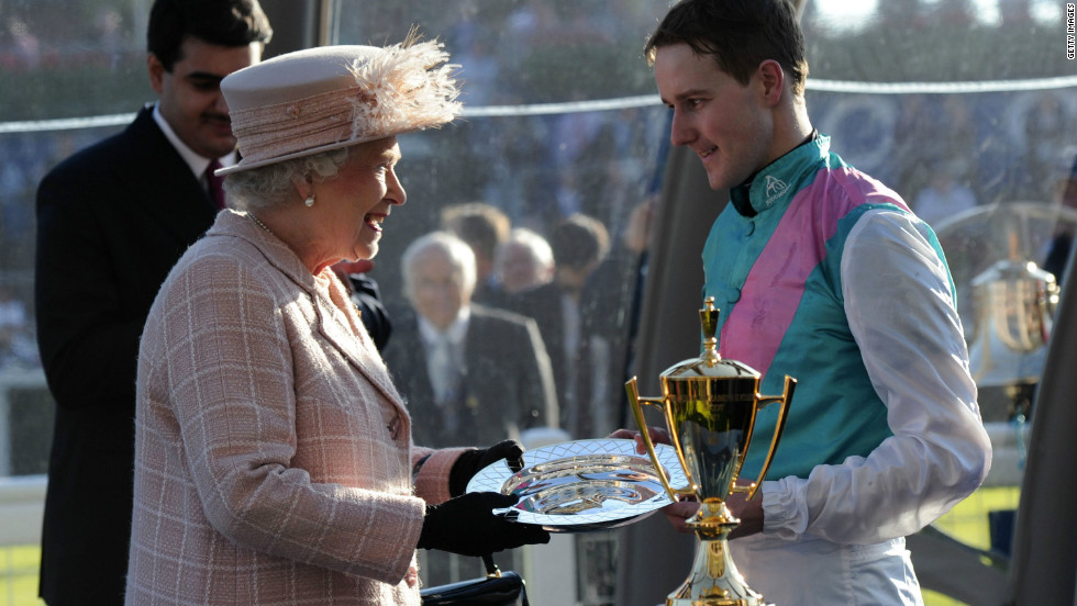 Queen Elizabeth II presents Frankel's jockey Tom Queally with the Champion Stakes trophy at Ascot.