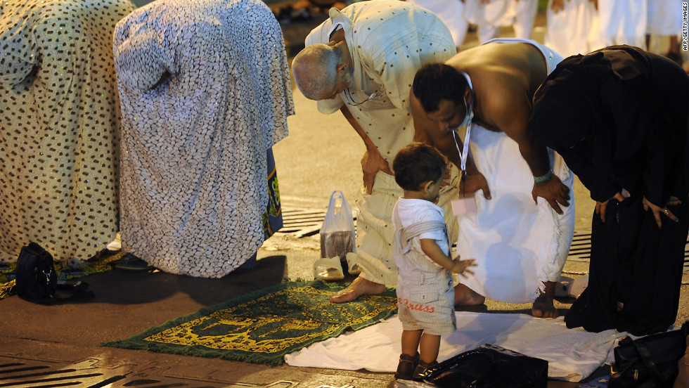 A child looks on as Muslim pilgrims perform evening prayers along a street close to the Grand Mosque in the holy city of Mecca on Tuesday.