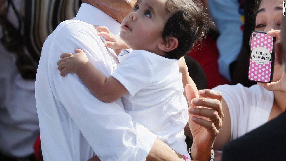 President Obama holds a baby as he greets people during a campaign rally at the Delray Beach Tennis Center on Tuesday, October 23, in Delray Beach, Florida. Obama continues to campaign across the United States in the run-up to the November 6 presidential election.