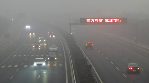 """Vehicles make their way along a highway as fog covers most of Beijing on March. Thick fog and air pollution covered the city dropping to """"hazardous"""" level in early March this year."""