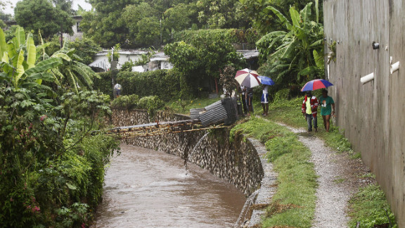 Jamaicans shelter themselves from the rain of approaching Hurricane Sandy as they walk along the Hope River on Wednesday.