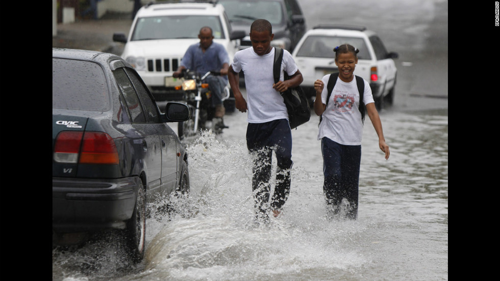 Students walk in floodwater from Hurricane Sandy's rain in Santo Domingo on Wednesday.
