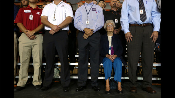 Supporters look on as Romney speaks during a campaign rally at Jet Mach