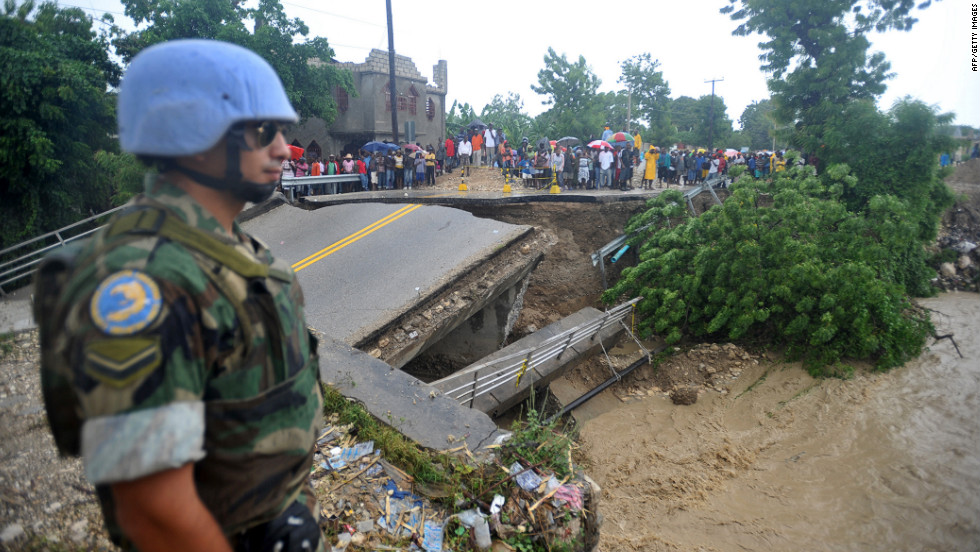 A U.N. peacekeeper on Thursday stands at the edge of a bridge that was washed away by heavy rains from Hurricane Sandy in Port-au-Prince, Haiti.