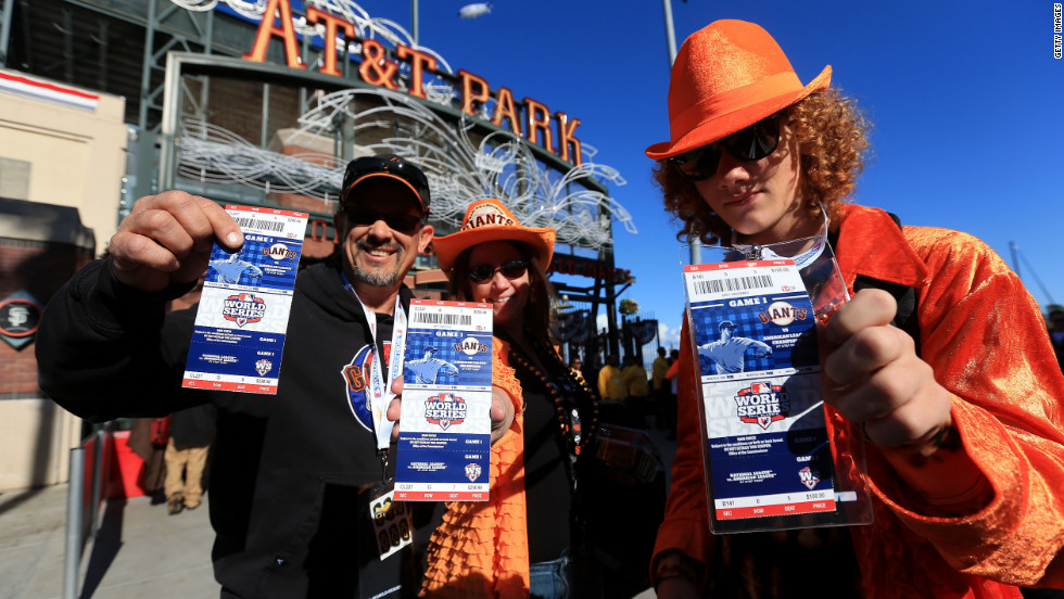 San Francisco Giants fans hold up their tickets to the game outside the stadium.
