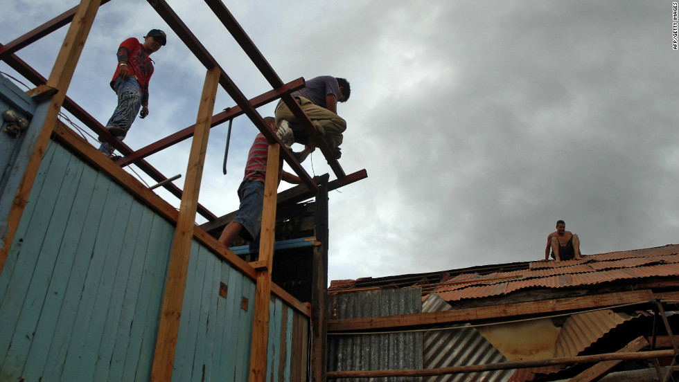 Residents in Bayamo, Cuba, try to fix a house damaged by hurricane Sandy on Thursday.