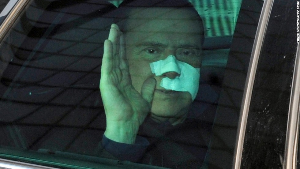 Berlusconi waves to journalists as he leaves a Milan hospital in December 2009 after suffering severe facial wounds in an attack at a rally.