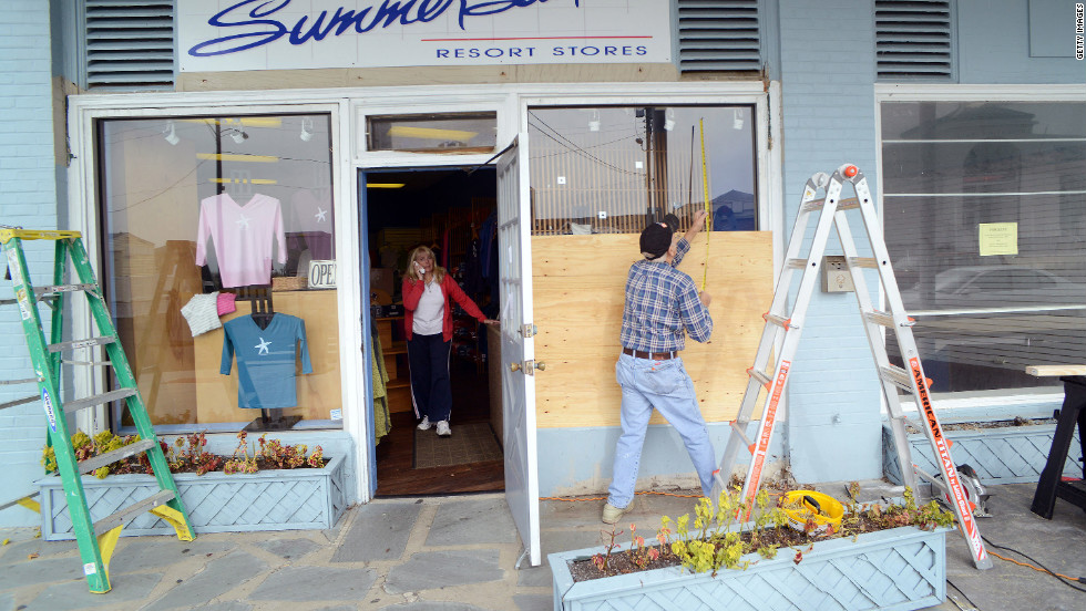 Bob Kaege takes a measurement while boarding up a shop in Cold Spring, New Jersey, on Saturday as Marie Jadick speaks on the telephone getting an updated weather report in preparation for Hurricane Sandy.
