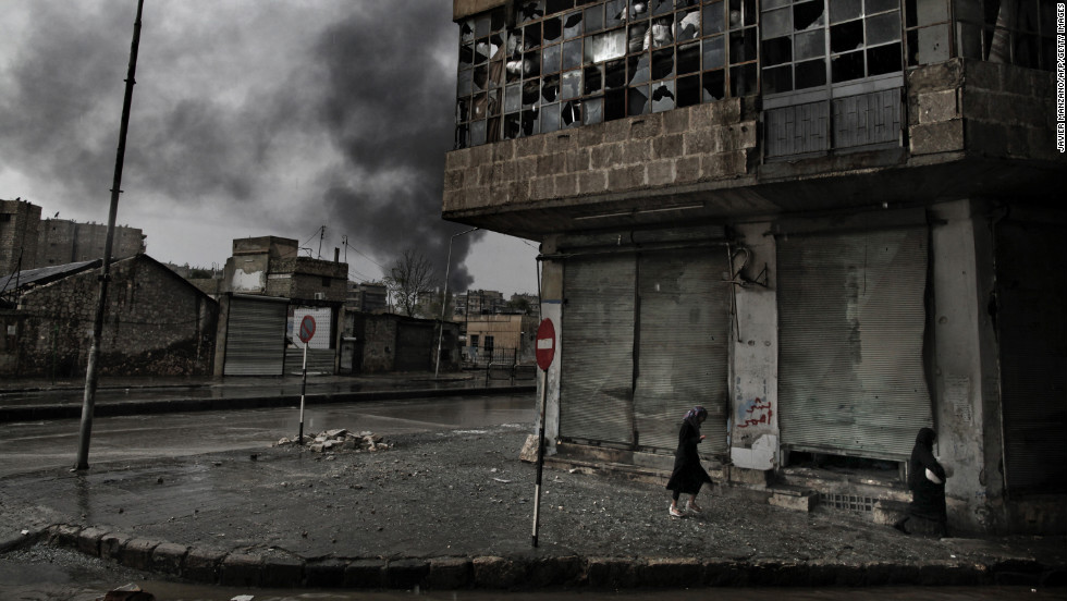 Smoke rises from a fuel station following a mortar attack as Syrian women walk on a rainy day in the Arqub neighborhood of Aleppo on October 25, 2012.
