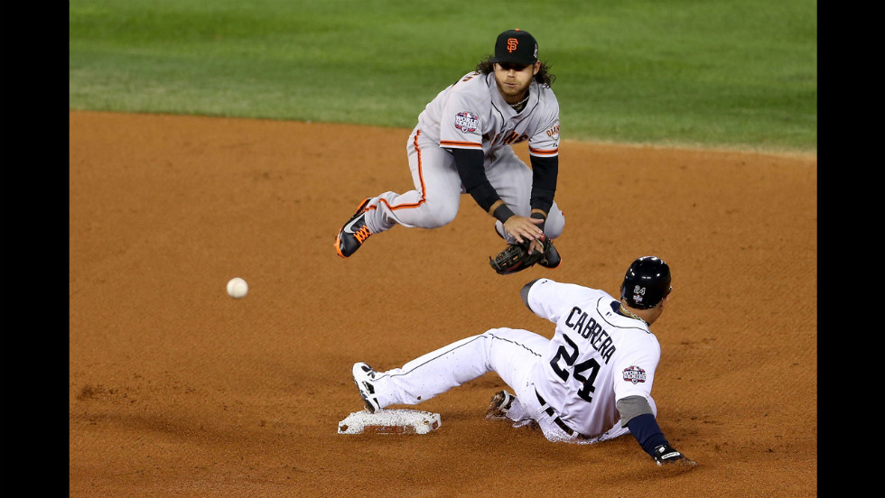 Brandon Crawford of the Giants dodges Miguel Cabrera of the Tigers on Saturday as he makes a double play to end the first inning.