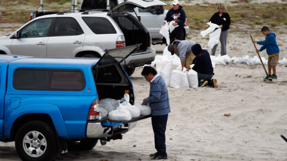 Residents of Long Beach, New York, fill sandbags on Sunday in preparation for the storm.