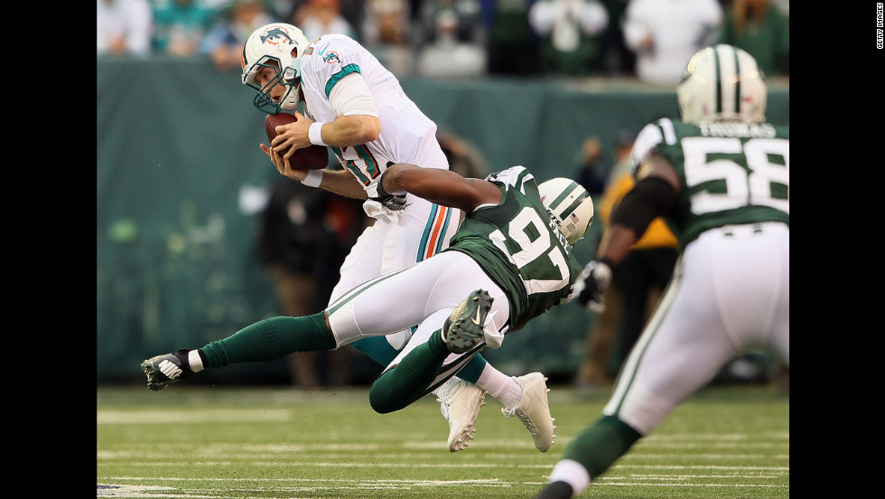 Quarterback Ryan Tannehill of the Miami Dolphins is sacked by outside linebacker Calvin Pace of the New York Jets at MetLife Stadium on Sunday in East Rutherford, New Jersey.
