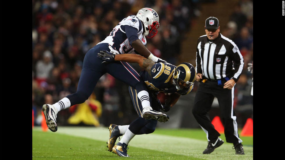 Lance Kendricks of the Rams is pushed out of bounds by Chandler Jones of the Patriots on Sunday.