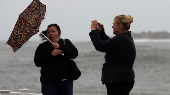 Lisa Cellucci holds her umbrella as it is blown backward by Hurricane Sandy