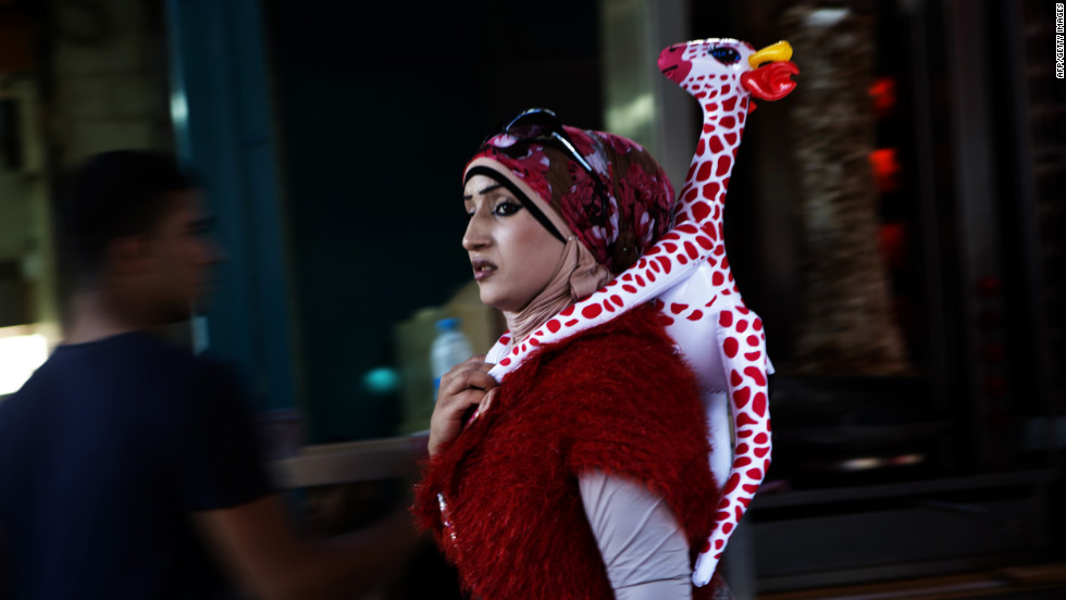 An Arab Israeli woman walks with an inflatable giraffe on her back during a festival on the second day of Eid al-Adha Sturday in Acre.