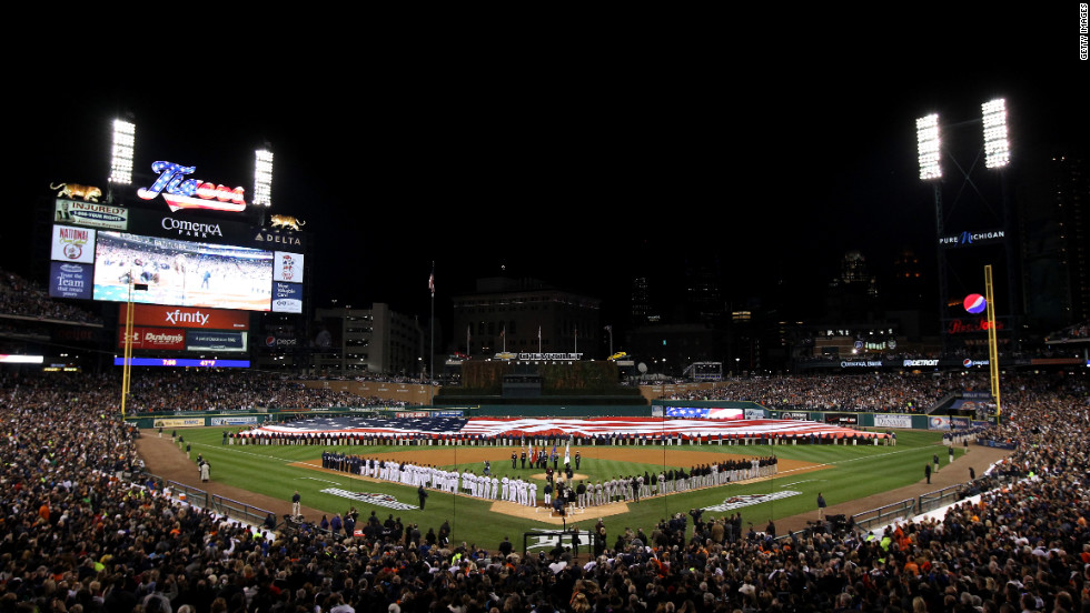 The Tigers and Giants line up on the field during the national anthem prior to Game 3.
