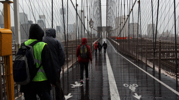 People walk across a rainy Brooklyn Bridge as New York City braces for Hurricane Sandy