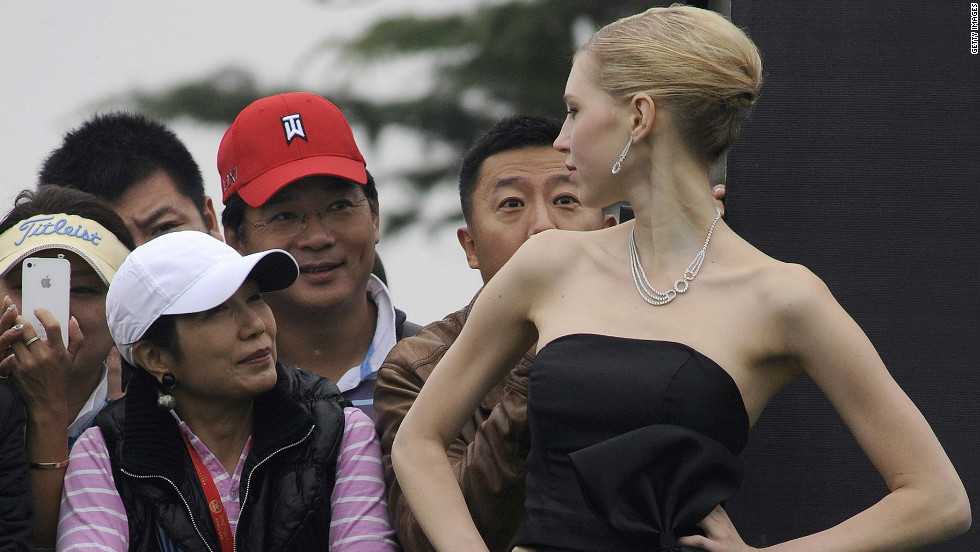 Local golf fans talk with one of the models who inhabited the greens in their evening wear in scenes seldom seen on any golf course.