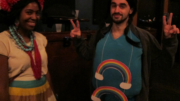 "The man on the right is sporting the Double Rainbow meme at the HallowMEME costume party.  The Double Rainbow became an Internet sensation after the video ""Yosemitebear Mountain Giant Double Rainbow 1-8-10"" went viral online."