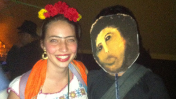 Alice Feigel, dressed as Frida Kahlo on the left, is standing next to Internet meme Botched Ecce Homo Painting. The meme when viral online after the failed restoration of a century-old fresco of Jesus Christ.