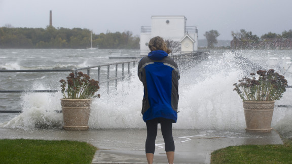 A woman watches waves crash onto a pier on New York