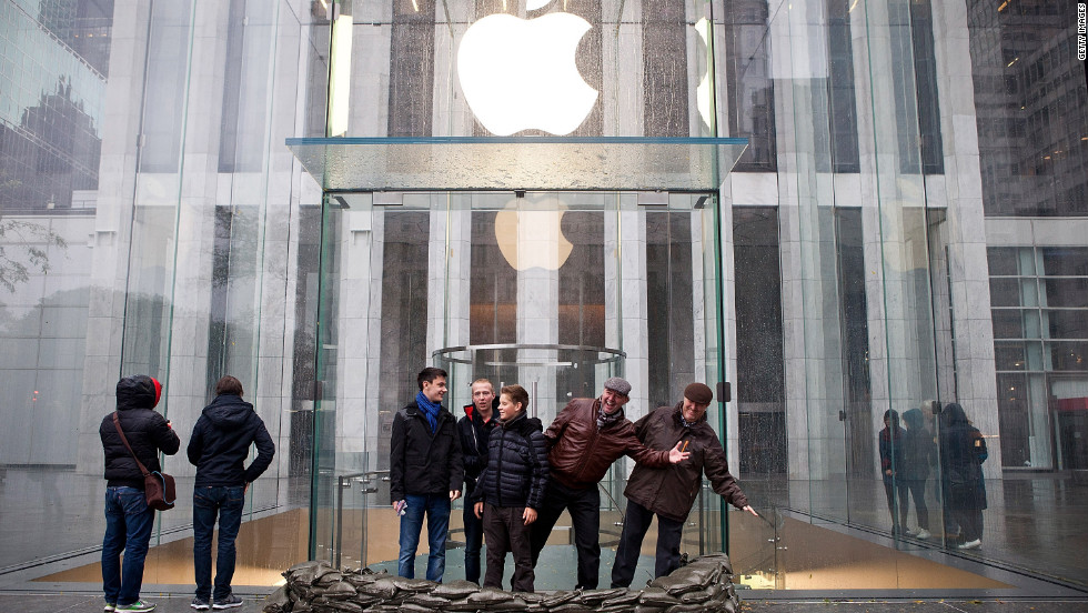 People pose outside the sandbagged entrance of the closed Fifth Avenue Apple Store on Monday.