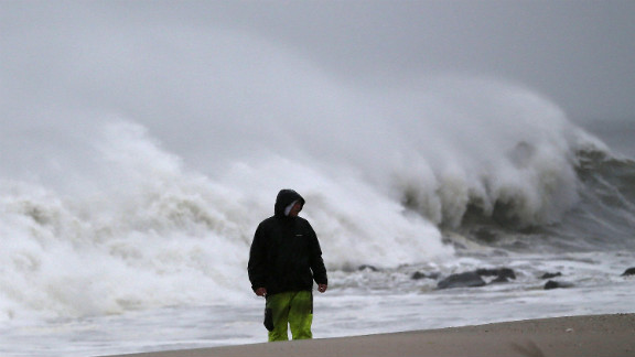 A man stands on the beach as heavy waves pound the shoreline Monday in Cape May, New Jersey.