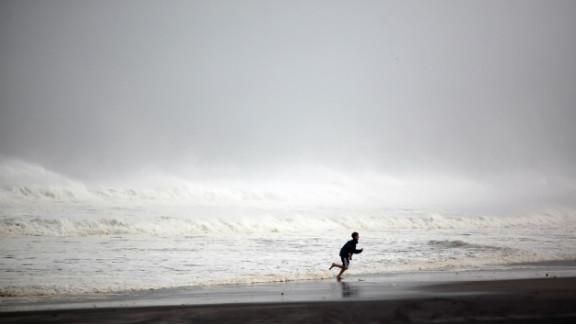 A young boy runs along Rockaway Beach in the Queens, New York, on Monday.