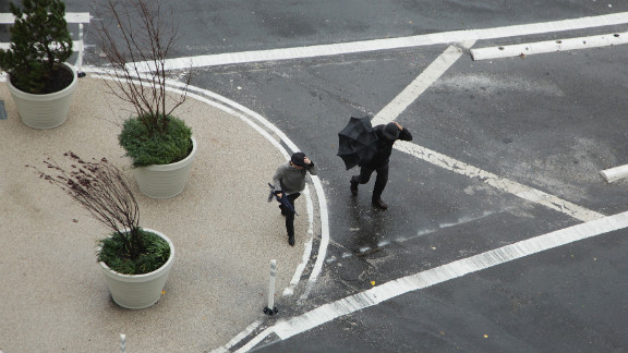 Two people cross the street near the closed Holland Tunnel on Monday as Hurricane Sandy moves up the coast.