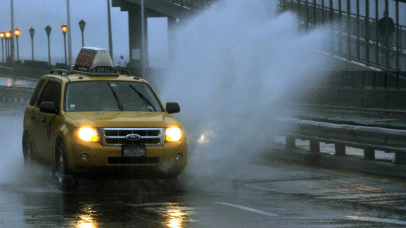 A car goes through standing water along FDR Drive as New Yorkers venture out into the stormy conditions on Monday, October 29.