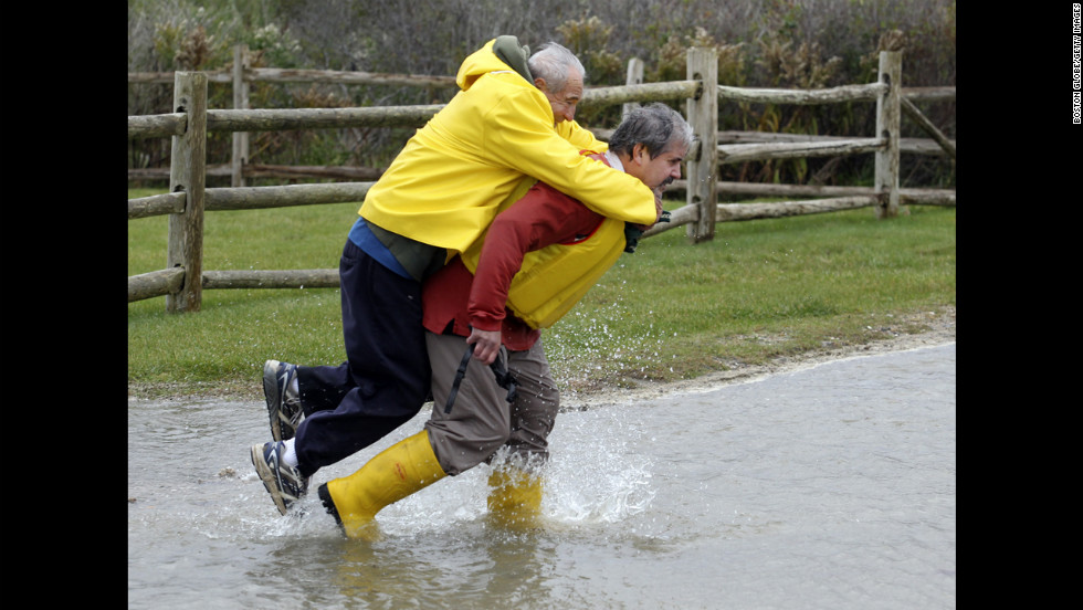 Chris Losordo carries his father, Vin, across a flooded road in Falmouth, Massachusetts, on Monday.
