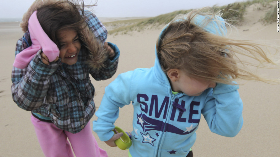 Jillian Webb, left, and Arianna Corso are pelted by wind and sand on Lighthouse Beach in Chatham, Massachusetts, on Monday.