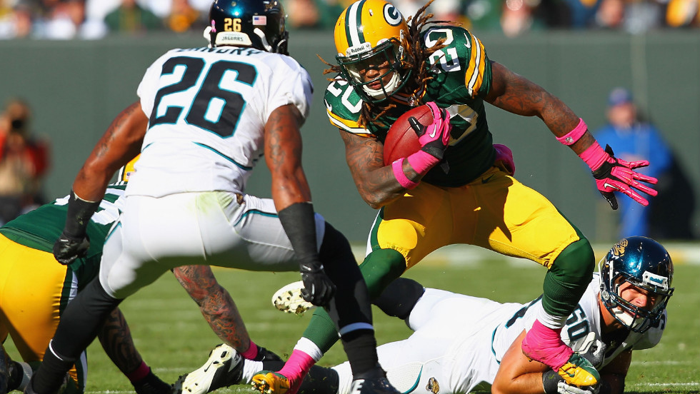 Packers No. 20 Alex Green tries to avoid being tackled by Jaguars players on Sunday.