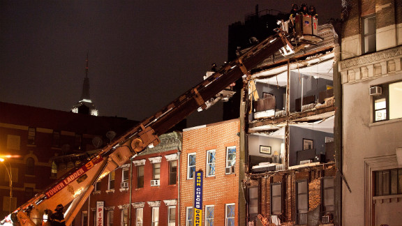 Firefighters evaluate an apartment building in New York that had the front wall collapse during the storm on Monday.