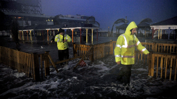 People walk through water on the beach near high tide Monday as Sandy approaches Atlantic City.