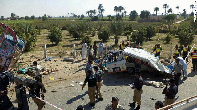 Pakistani police officials are pictured on the scene of a highway accident near Bahawalpur town on Tuesday.