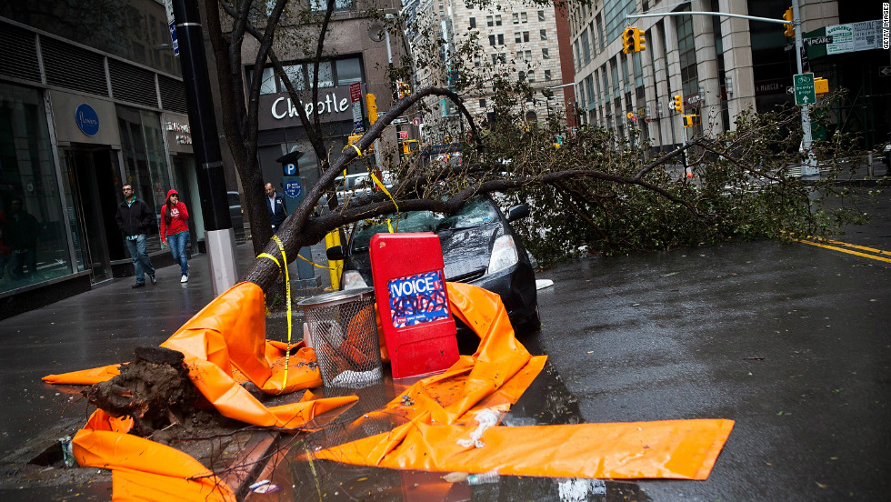"A car sits crushed by a tree in the Financial District on Tuesday. <a href=""http://www.cnn.com/2012/10/29/us/gallery/ny-braces-sandy/index.html""><strong>Photos: New York braces for Sandy</a><strong></strong>.</strong>"