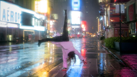 A visitor does a cartwheel in the rain in New York