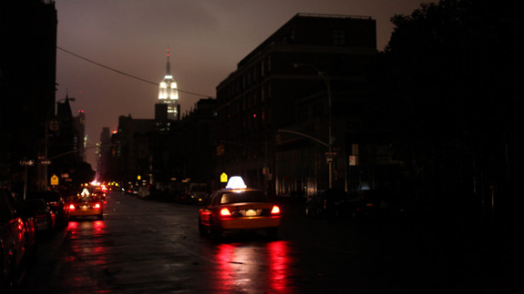 Taxis drive down a New York street where the power was out late Monday, October 29.