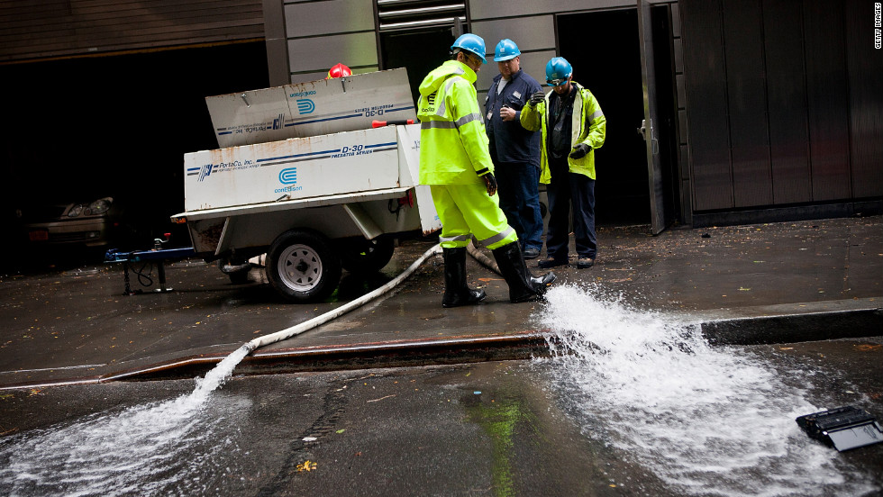 Con Edison employees monitor the drainage of water being pumped out of Seven World Trade Center in the Financial District of New York on Tuesday.