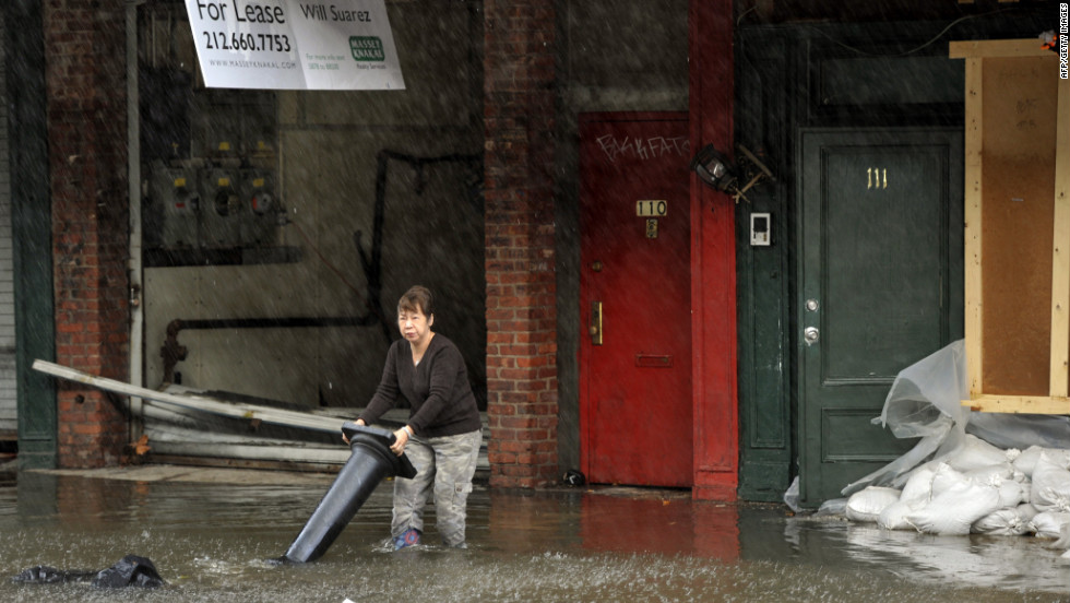 A woman wades through water at the South Street Seaport in New York City on Tuesday.