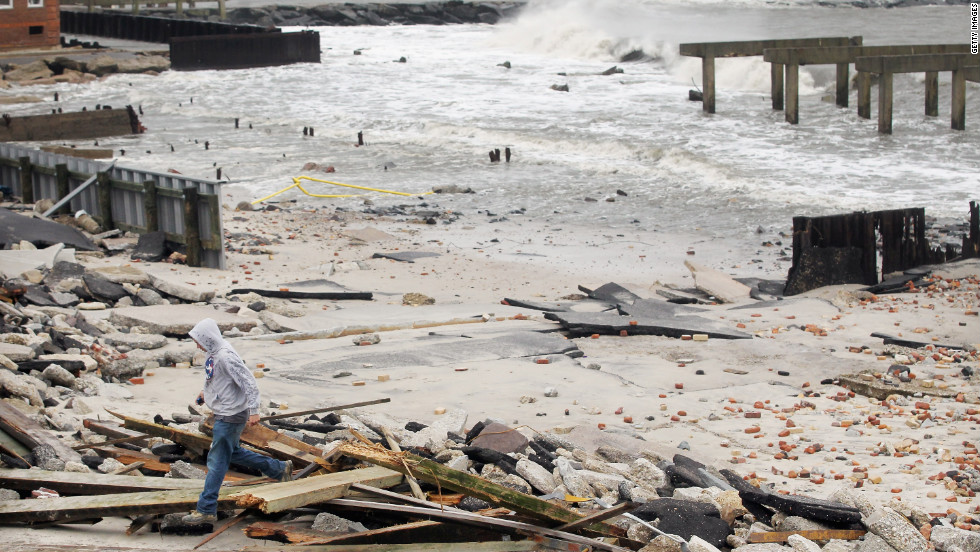 "A man walks through the debris of a 2,000-foot section of Atlantic City, New Jersey's ""uptown"" boardwalk on Tuesday. It was destroyed by flooding from Sandy."