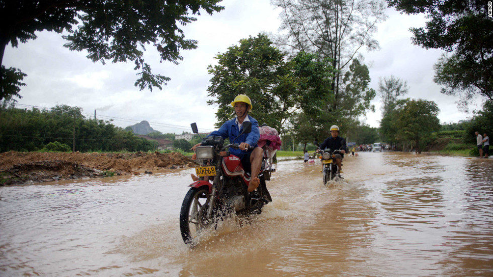 Citizens ride on a flooded road in Beiliu, China, on Tuesday.